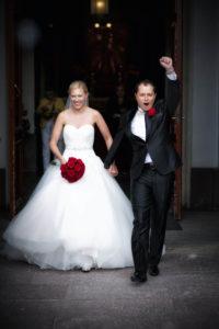 Bruden och brudgummen kommer ut från kyrkan efter bröllopet